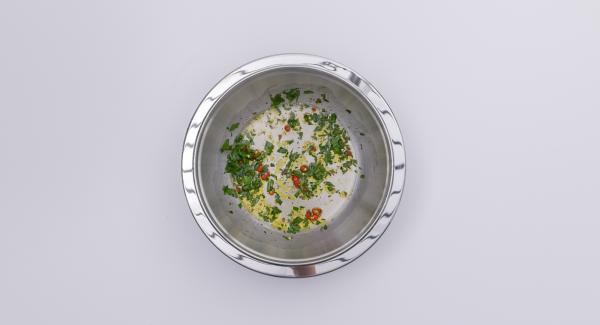 Picar las hojas de perejil. Picar la guindilla en dados pequeños. Mezclar con aceite y vinagre hasta formar un aderezo y sazonar con sal y pimienta.