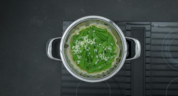 Cuando el Avisador (Audiotherm) emita un pitido al finalizar el tiempo de cocción, retirar el Navigenio, Repartir el pan rallado sobre la masa, distribuir los guisantes, añadir la cebolla y el jamón. Verter la mezcla de crema  y espolvorear con el queso. Apagar el fuego.