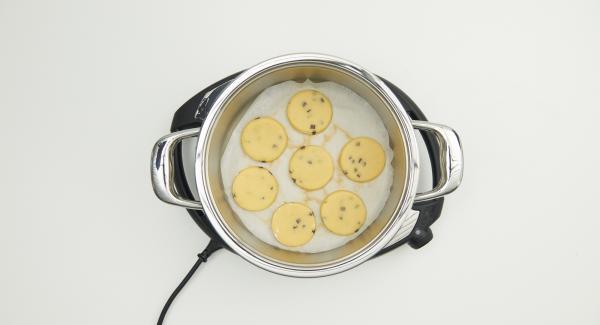 """Cuando el Avisador (Audiotherm) emita un pitido al llegar a la ventana de """"chuleta"""", colocar el papel de horno en la olla e introducir las porciones de masa encima."""