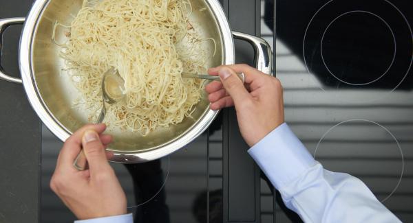 Dorar la pasta vigorosamente y retirarla. Freír brevemente las cebolletas, el pimiento, la guindilla, el ajo y el jengibre. Añadir los langostinos y freírlos.