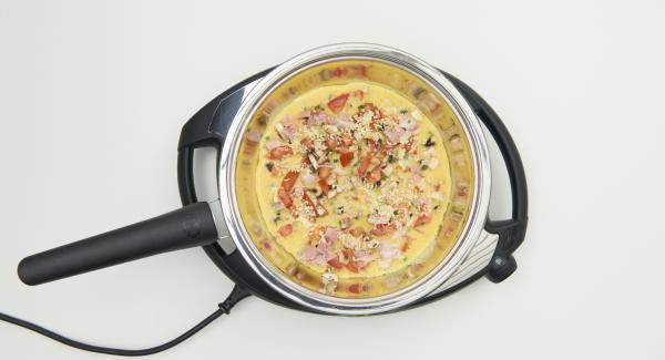 """Cuando el Avisador (Audiotherm) emita un pitido al llegar a la ventana de """"chuleta"""", apagar el Navigenio. Verter la mitad de la mezcla de huevo en la sartén, distribuir la mitad de los otros ingredientes sobre ella y espolvorear con una cucharada de queso."""