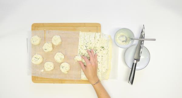 Cortar la masa en tiras de unos 2 cm de ancho y enrollarlas. Presionar los caracoles ligeramente hacia abajo.
