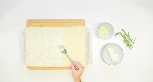 Untar la masa de pizza con la crema de queso a las hierbas.