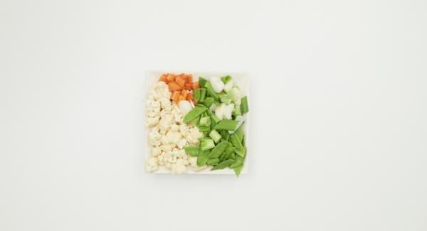 Limpiar la coliflor, los tirabeques y las cebolletas y pelar la zanahoria. Cortar las verduras en trozos del tamaño de un bocado.