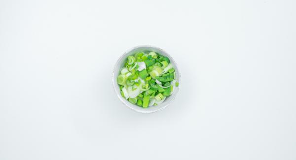 Cortar la pechuga de pollo en tiras y sazonar con la salsa de soja. Limpiar las cebolletas y cortarlas en aros finos.