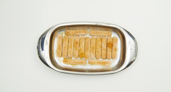 Disponer  una capa de bizcochos en la lasañera, añadir la mitad del zumo de naranja y remojar los bizcochos.