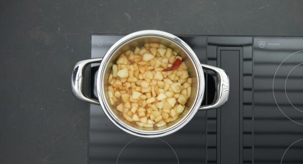Añadir la manzana, la pera y la guindilla, desglasar con Calvados o ron y dejar evaporar. Agregar el vino y el zumo de manzana, hervir todo hasta que esté cremoso. Retirar la guindilla al final.