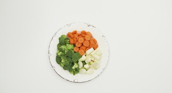 Limpiar las verduras, cortarlas en trozos iguales y ponerlas en la olla mojadas. Cortar las cebolletas y añadirlas.