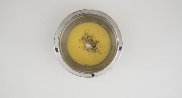 En un bol, batir los huevos. Añadir el queso parmesano rallado y sazonar con sal y pimienta.