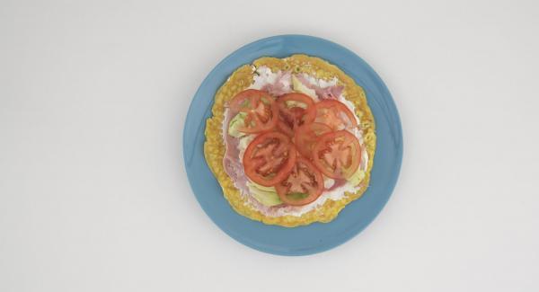 Lavar y cortar el tomate en rodajas. Extender el queso crema sobre la tortilla, colocar las lonchas de jamón, la lechuga y por último los tomates encima.