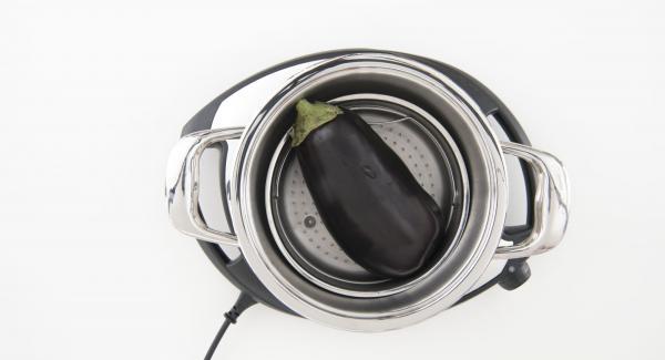 """Verter agua (unos 150 ml) en una olla. Poner la berenjena en la Softiera e introducir en la olla. Tapar con la Tapa Rápida (Secuquick Softline). Colocar la olla en el Navigenio a temperatura máxima (nivel 6). Encender el Avisador (Audiotherm), introducir 3 minutos de tiempo de cocción. Colocarlo en el pomo (Visiotherm) y girar hasta que aparezca el símbolo de """"soft""""."""