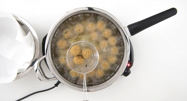 Al alcanzar los 90 °C, dar la vuelta a las albóndigas y terminar de freír hasta que se doren. Escurrir y secar sobre papel de cocina. Servir caliente.