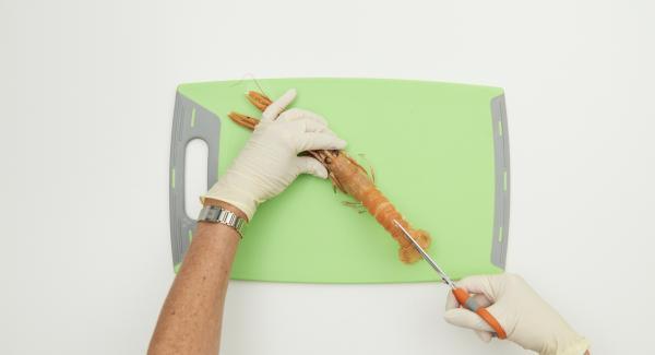 Cortar la cáscara de las cigalas por el lomo con unas tijeras y extraer con cuidado el hilo negro del intestino. Luego cortar por la mitad, a lo largo, con un cuchillo grande. Lavar con agua fria y secar con papel de cocina.