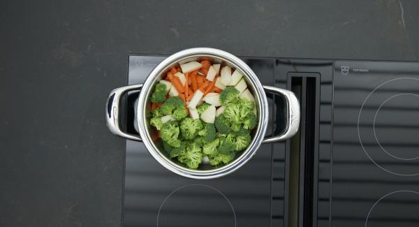 """Introducir las verduras cortadas y sin escurrir en la olla . Colocar la olla en el fuego a temperatura máxima. Encender el Avisador e introducir 8 minutos de tiempo de cocción. Colocarlo en el pomo y girar hasta que aparezca el símbolo de """"zanahoria"""". Cuando el Avisador emita un pitido al llegar a la ventana """"zanahoria"""", bajar temperatura y cocinar hasta el final."""