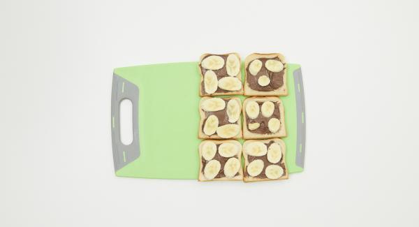Extender la crema de chocolate sobre la mitad de las tostadas. Pelar el plátano, cortarlo en rodajas y repartirlo sobre las tostadas. Cubrir con el resto de las tostadas.