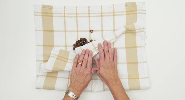 Poner las avellanas sobre un paño de cocina y retirar la piel marrón frotándolas vigorosamente.