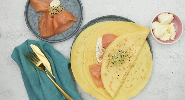 Untar el queso cremoso mezclado con rábano picante y salmón ahumado sobre las crepes frías.