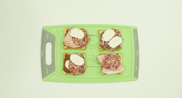 Untar la mitad de las rebanadas de pan con el pesto rojo o verde. Añadir el gouda o la mozzarella y el jamón dulce o salami y colocar una rebanada encima.