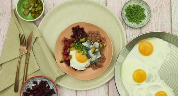 Servir al gusto. Puedes mezclar la carne con la masa de remolacha y patata, colocar un huevo frito encima, añadir los pepinillos cortados y las anchoas.