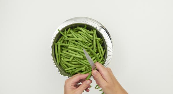 Limpiar los frijoles y cortarlos en trozos pequeños. Pelar y picar la cebolla finamente.