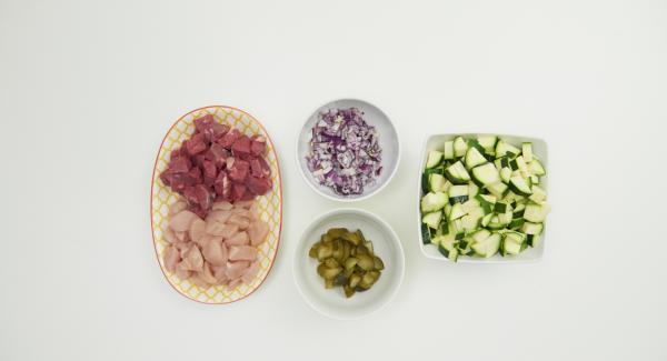 Cortar el pollo y la carne en dados de 1 a 2 cm. Cortar en trozos pequeños el calabacín, la cebolla y los pepinillos escurridos.