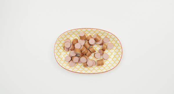 Al finalizar el tiempo de cocción, dejar despresurizar y retirar. Cortar las salchichas en rodajas y añadirlas a la olla.