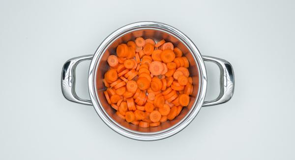 Pelar las zanahorias, cortarlas en rodajas y ponerlas en una olla.