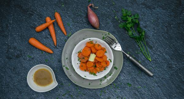 Picar finamente las hojas de perejil y espolvorear sobre las zanahorias.