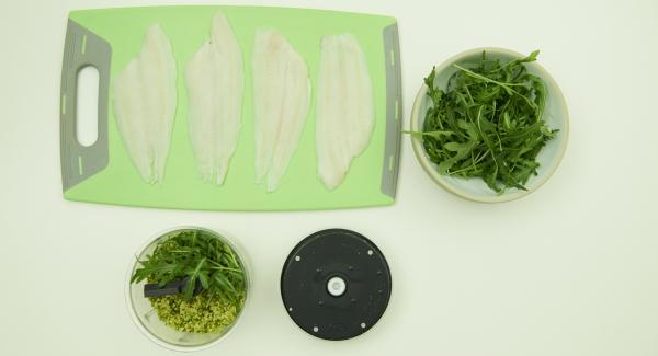 Colocar los filetes de pescado en una tabla. Introducir el parmesano y los pistachos en Quick Cut y picar finamente. Añadir el la rúcula y picar. Agregar el aceite de oliva, sazonar con sal, pimienta y mezclar.