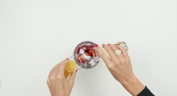 Incorporar las fresas limpias y cortadas en un recipiente, añadir el zumo de naranja, 2 cucharadas de azúcar, el licor y batir.