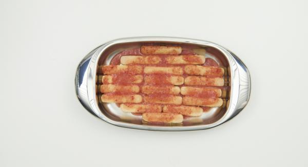 En la lasañera mediana, colocar los melindros de manera ordenada y verter la mitad de la salsa de fresas.