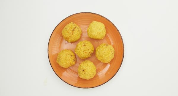 Para realizar las bolas, con una mano, coge un poco de risotto y colócalo en la palma de la mano. Añade en el centro del risotto, un poco del relleno de carne y envuelve el relleno con el arroz hasta formar una bola. Al final tendrás una bola de arroz por fuera y rellena de carne por dentro.
