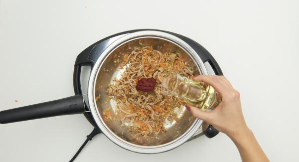 Añadir el concentrado de tomate, el vino blanco y rehogar.