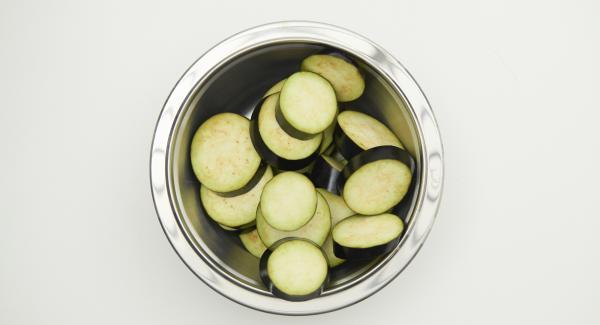 Limpiar las berenjenas y cortarlas en rodajas de 1,5 cm de grosor. En un bol, mezclar 1 cucharada de aceite, agua  y añadir las especias, la harina de garbanzo, la harina de arroz, el almidón de maíz y sazonar con sal.