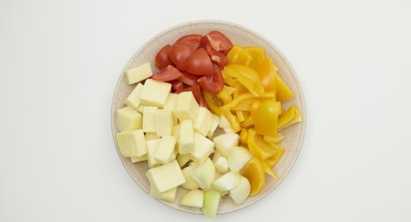 Pelar las cebollas, limpiar el tomate, el pimiento y cortar todo en trozos gruesos del tamaño de los dados de tofu.