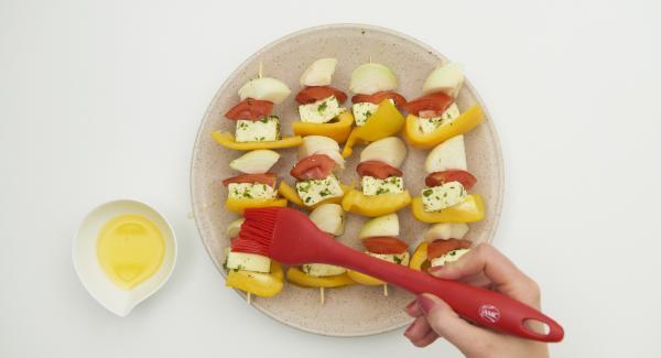 Colocar todas las verduras preparadas y los dados de tofu alternativamente en cuatro brochetas de madera. Con un pincel, pintar las brochetas con la mantequilla derretida.