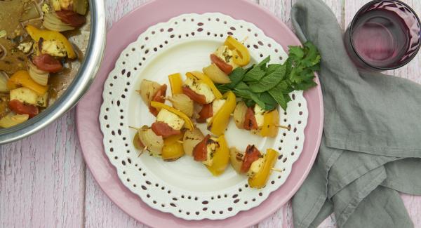 Servir las 9 brochetas con el resto del aliño, la rodaja de limón, los aros de cebolla y las hojas de menta.
