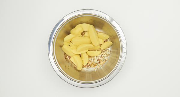 En un bol, mezclar el aceite de oliva, el pimentón, el curry en polvo, sazonar con sal y pimienta. Añadir las patatas y el ajo, mezclar y dejar reposar.