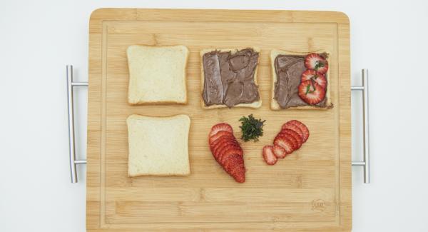 Untar dos rebanadas de pan tostado la crema de chocolate y avellanas. Limpiar las fresas y cortar en lonchas finas. Picar finamente las hojas de menta y espolvorear un poco en la tostada.