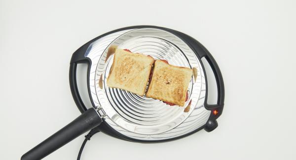 Bajar temperatura de Navigenio nivel 2, introducir los sandwiches en la oPan. Cuando se haya tostado, dar la vuelta y tostar por el otro lado.
