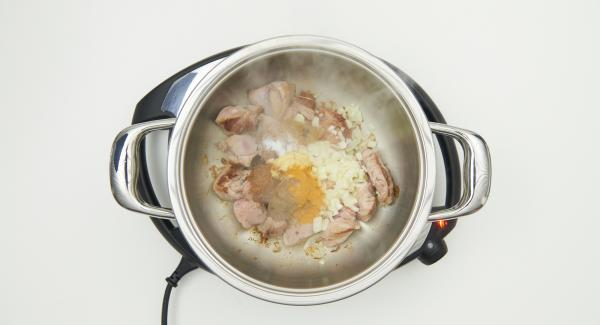"""Cuando el Avisador emita un pitido al llegar a la ventana de """"chuleta"""", dar la vuelta a la carne y añadir la cebolla, la pasta de jengibre, las especias, los tomates cortados y sazonar. Tapar con la Tapa Rápida."""
