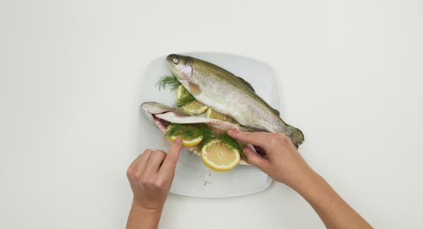Lavar la trucha con agua fría y secar dando pequeños golpecitos. Sazonar el interior con sal y pimienta, añadir 2 rodajas de limón y 2 ramas de eneldo.