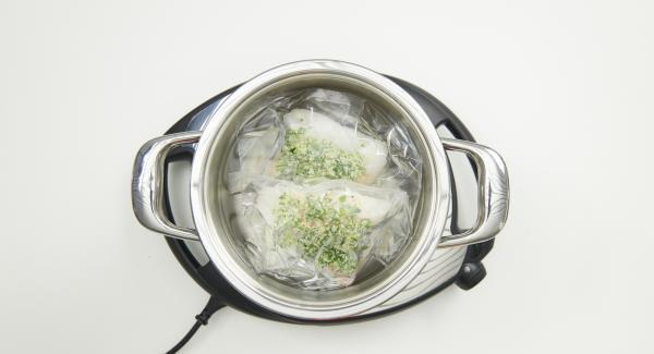 Colocar la olla en Navigenio, verter aprox. 3 litros de agua. Introducir la bolsa de vacío con el pescado y tapar.