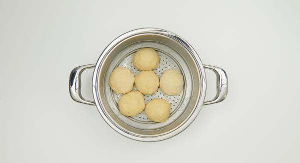 Engrasar el Accesorio Súper-Vapor con un poco de mantequilla. Dividir la masa en seis trozos, y moldearla en forma de bola, rellenar cada uno con un trozo de chocolate, cubrirlo bien y enrollarlo. Colocarlos en el Accesorio Súper-Vapor.