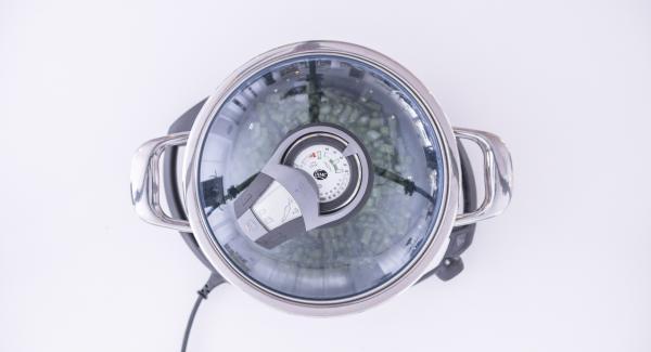 """Cuando el Avisador (Audiotherm) emita un pitido al llegar a la ventana de """"chuleta"""", añadir los guisantes y los espárragos y saltear. Verter el vino blanco. En el Navigenio, seleccionar la función """"A"""", encender el Avisador (Audiotherm), introducir 10 minutos de tiempo de cocción. Colocarlo en el pomo (Visiotherm) y girar hasta que aparezca el símbolo de """"zanahoria""""."""
