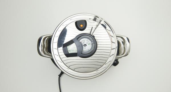 """Colocar el Accesorio Súper-Vapor encima de la olla y colocar la Tapa Súper-Vapor con el aro de sellado de 24 cm. Colocar en el Navigenio y seleccionar la función """"A"""". Encender el Audiotherm Plus, introducir aprox. 12 minutos de tiempo de cocción. Cuando aparezca el símbolo """"+"""", introducir el tiempo de inicio planificado (momento en el que se quiere iniciar la cocción). Colocarlo en el pomo (Visiotherm) girar hasta que aparezca el símbolo """"vapor""""."""