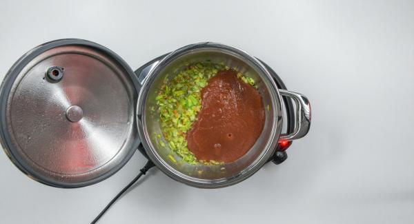 """Añadir el tomate (en conserva), el caldo de verduras, las 2 cucharadas soperas de aceite de oliva y pimienta. Colocar una olla en el Navigenio y seleccionar la función  """"A"""", encender el Avisador (Audiotherm), introducir 5 minutos de tiempo de cocción. Colocarlo en el pomo (Visiotherm) y girar hasta que aparezca el símbolo de """"vapor""""."""
