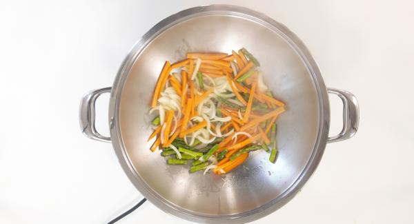 Cuando el Avisador emita un pitido al llegar a la ventana de chuleta, añadir la cebolla, las zanahorias, los espárragos un poco de aceite y saltear bien.