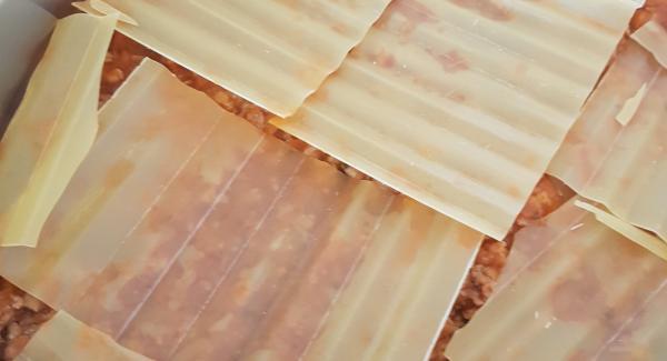 A)  En el fondo de la Oval ponemos el tomate crudo triturado. B) Ahora una tanda de placas de lasaña, sin necesidad de cocerlas previamente y seguido la mitad de la carne frita. C) Otra tanda de placas de lasaña y seguido el resto de la carne con la salsa . Terminamos de poner las ultimas placas que nos quedan. Una caja viene bien para completar la receta.