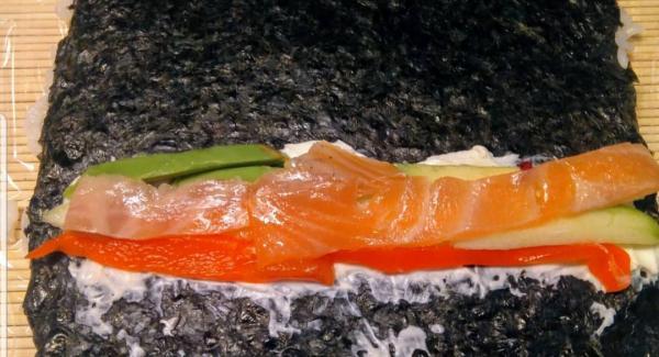 Con ayuda de un trozo de film, le damos vuelta dejando el arroz debajo y el alga encima. Ponemos un poco de queso crema y encima los ingredientes que más nos gusten